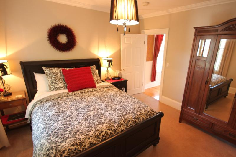 Queen Bedroom with black sleigh bed and antique armoire
