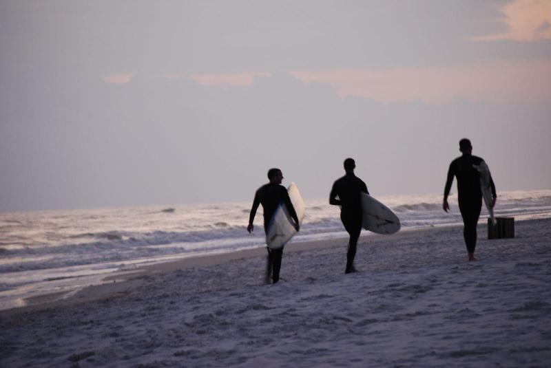 Surfers head home on beach in front of ES41
