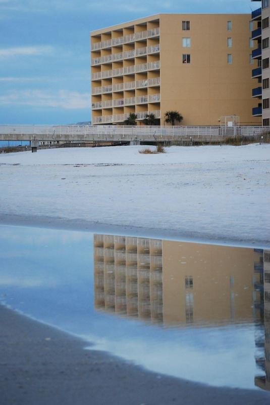 Early morning, building reflected in tidal pool.
