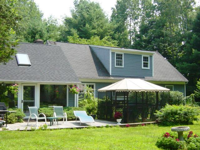 Main house with deck and screen house including lawn chairs and back yard