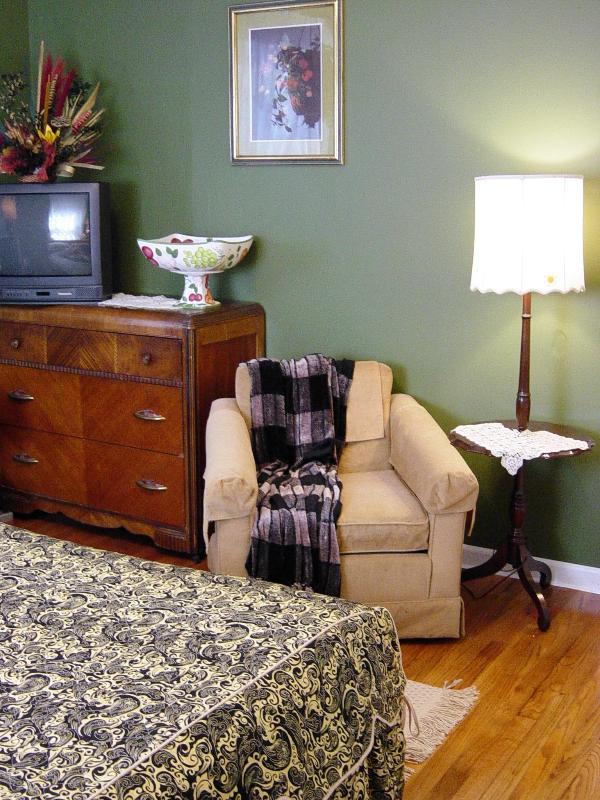 Green bedroom with queen bed.