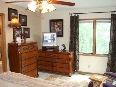 Master Suite has elegant furnishings, window with woodlands view