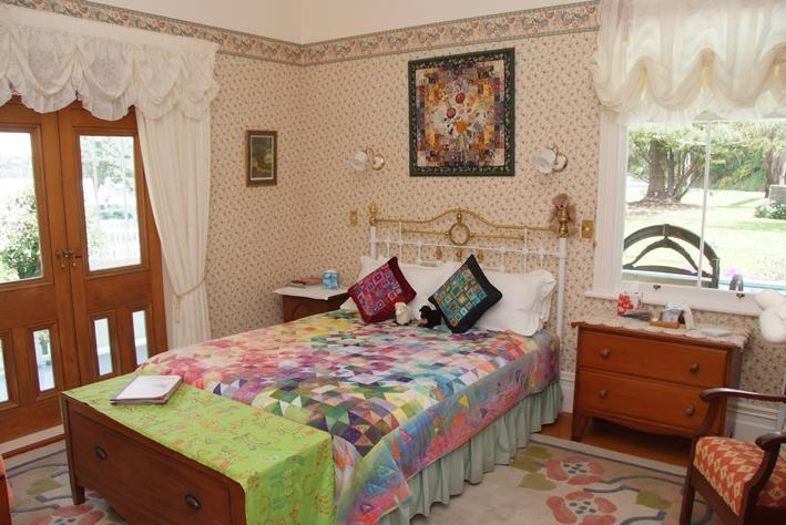 Knight room in the main guestlodge with queen bed opening onto the front verandah and conservatory