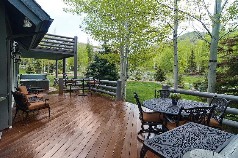 Deck at the back of house, beautiful yard and hot tub