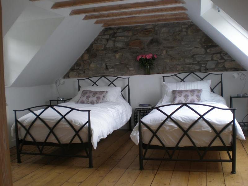 Twin bedroom with exposed stonework and beams