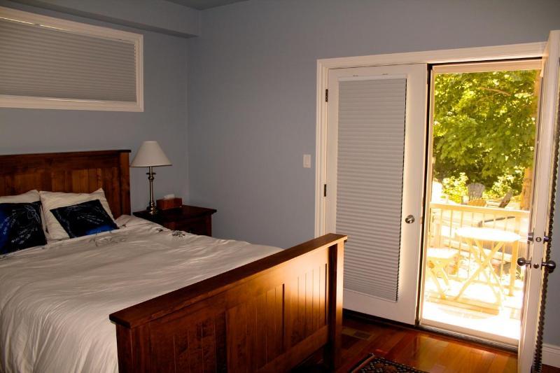 Main floor bedroom with balcony to backyard and hot tub