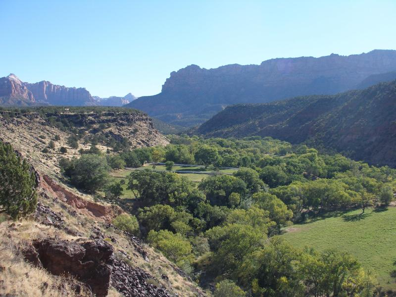 Ranch is located in a deep valley with a stream running through it