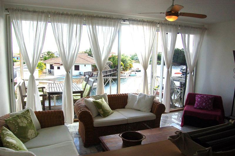 The living area with ceiling fan, view onto the water, mosquito screens on the sliding doors.
