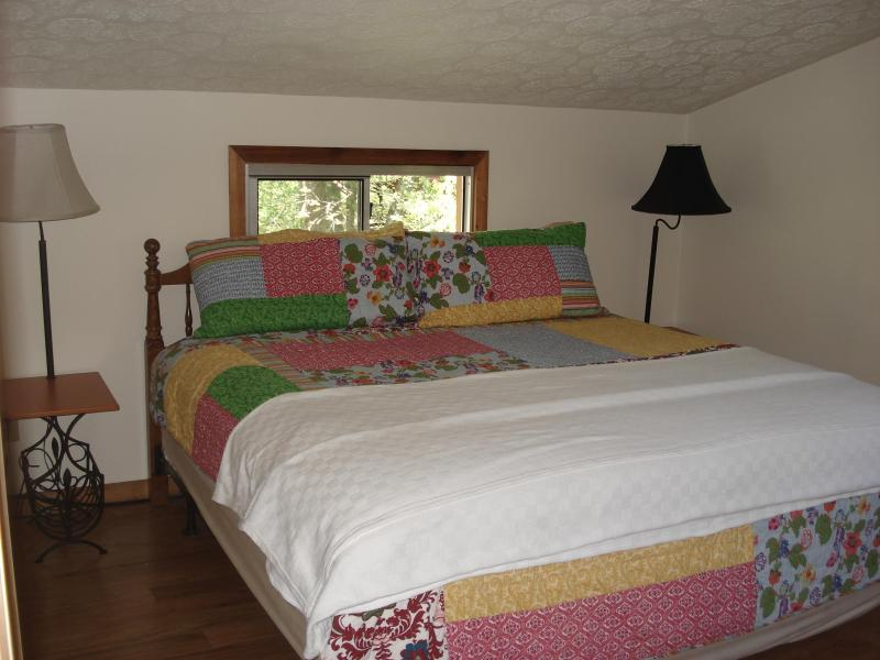 This spacious king bedroom includes ceiling fan, dresser, closet and luggage rack