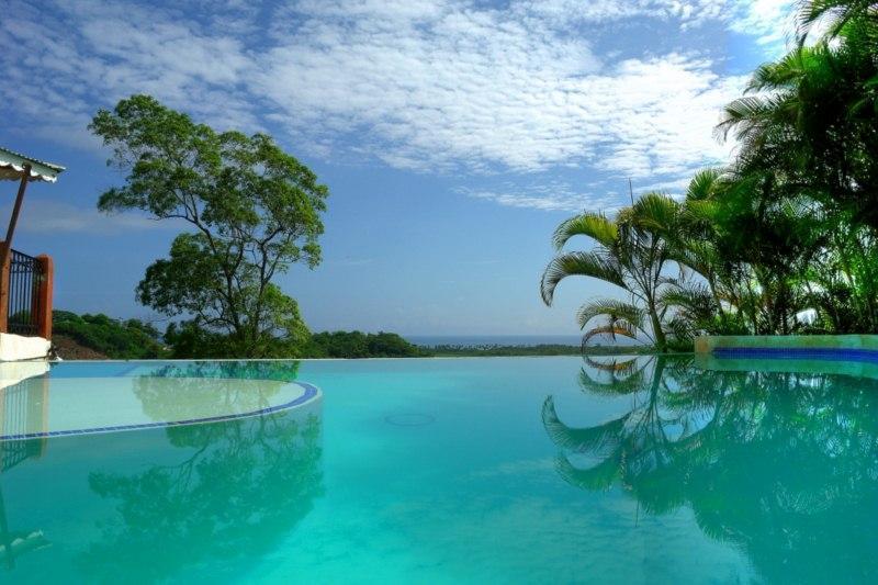 La piscina a sfioro cascata virtualmente nell'oceano in lontananza.