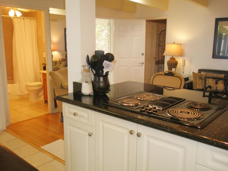 Kitchen cook top range with view to 2nd bath and back door to patio
