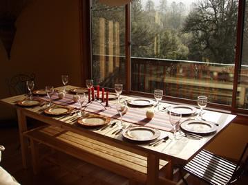 Mesa de comedor con grandes ventanales con vistas a la propiedad