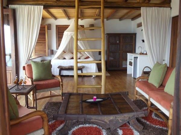 Full view of the main floor of Casa Coco.  King bed, living room area, kitchette and an upper loft