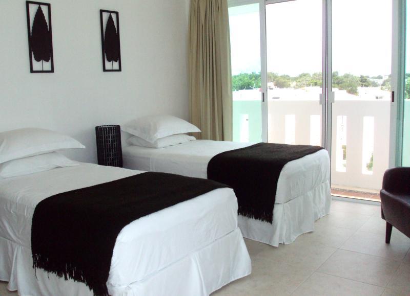 Chambre 2 - lits jumeaux avec chaise, réveil et beaucoup de stockage