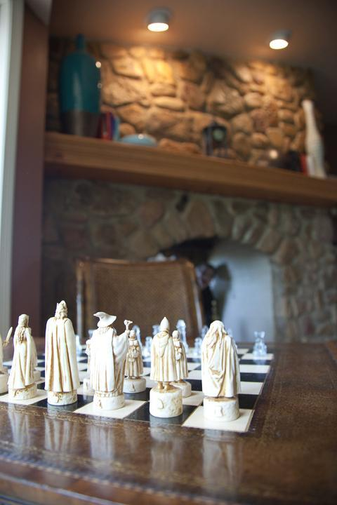 A Lord of the Rings chess set by the fireplace (of course)