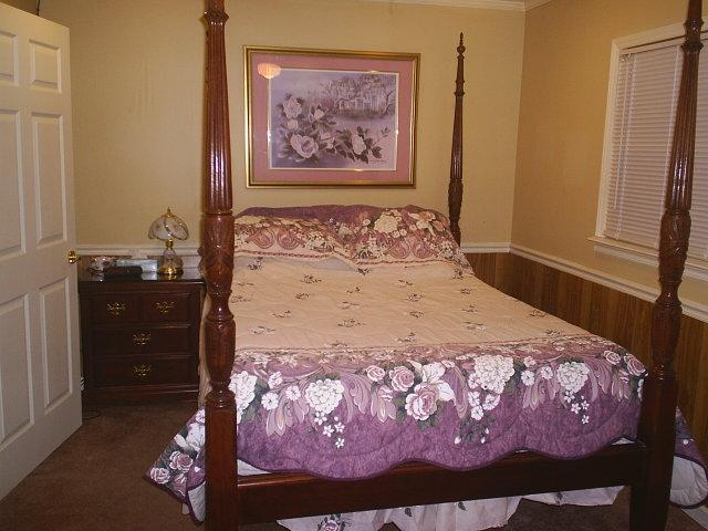 Bedroom with Queen four post rice bed has matching large dresser