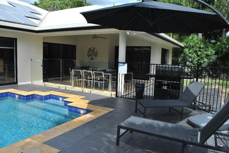 Poolside patio with couch & armchair seating, alfresco dining, BBQ & loungers