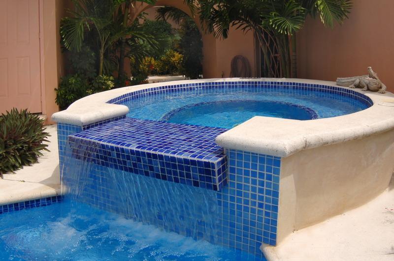 Bañera de hidromasaje de Juzzui y caída de agua en la piscina.