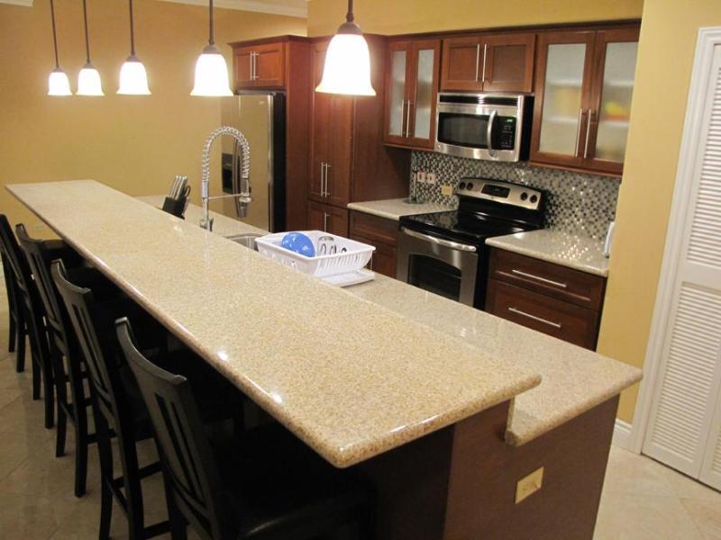 Cocina con electrodomésticos de acero inoxidable, encimeras de granito, asientos para 5 en barra desayunadora
