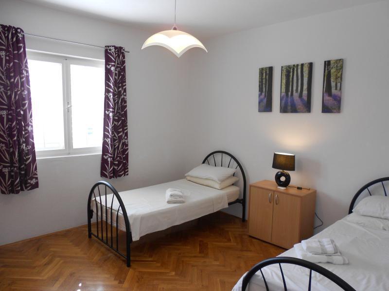 Grande deuxième chambre avec lits jumeaux et air conditionné.