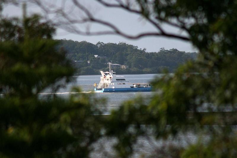 Een lokale aak vervoert auto's en naar Macelay, evenals de andere Southern Moreton Bay Islands