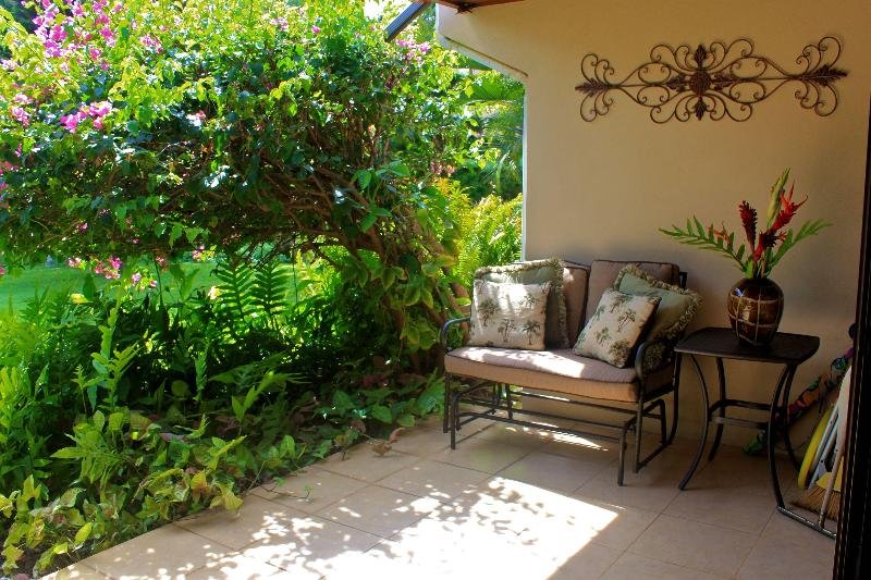 Glider on private Lanai looks out on expansive yard to olympic size pool