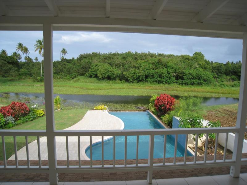 view of the pool and deck from the upstairs balcony