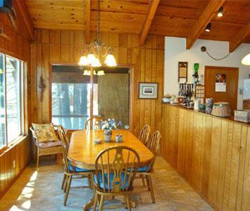 Comedor con vistas al lago y muebles de roble
