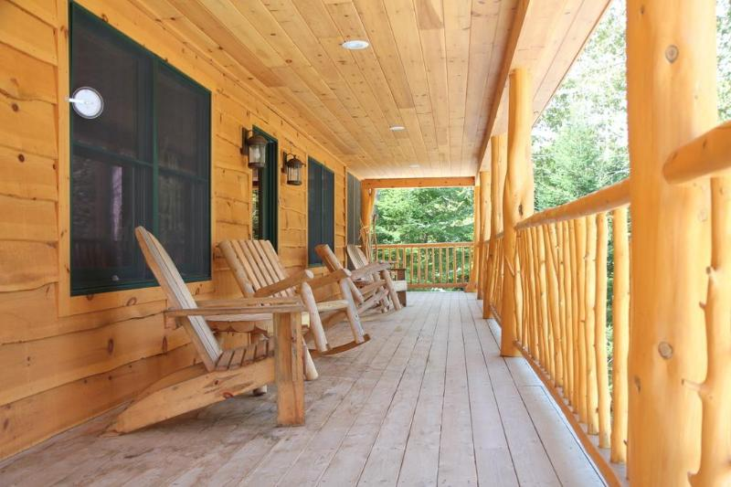 Expansive deck overlooking lake with seating, a picnic table, and gas grill.