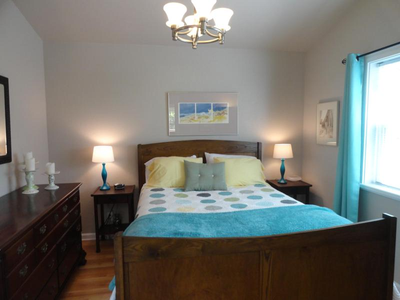 Bedroom with queen bed, large dresser and plush linens