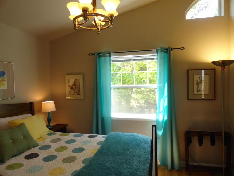 Bedroom with queen bed and large window