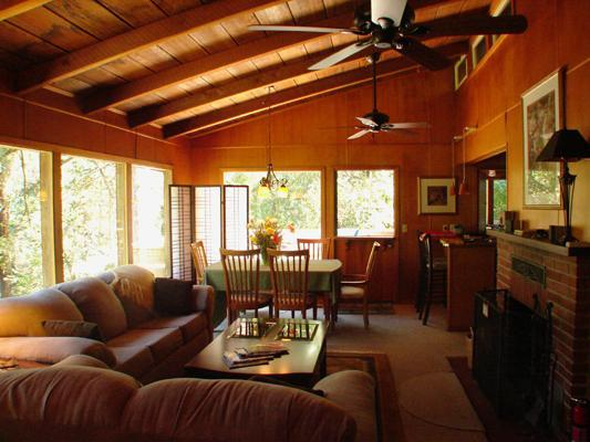 The living room with its panoramic windows on the woods
