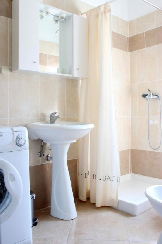 The bathroom provides a modern shower unit, as well as a hair dryer and washing machine.