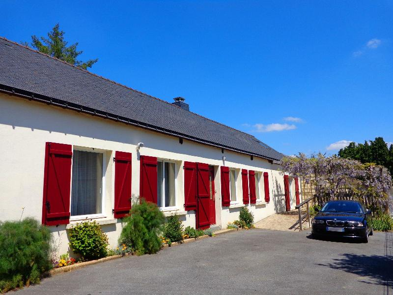 Ty Louisette Gite in the summer sunshine, front breakfast terrace covered in wisteria, parking.