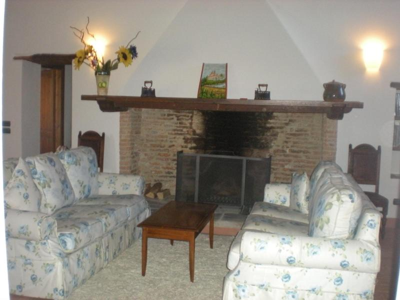 LARGE LIVING ROOM WITH WOODEN FIREPLACE on the first floor of the Villa