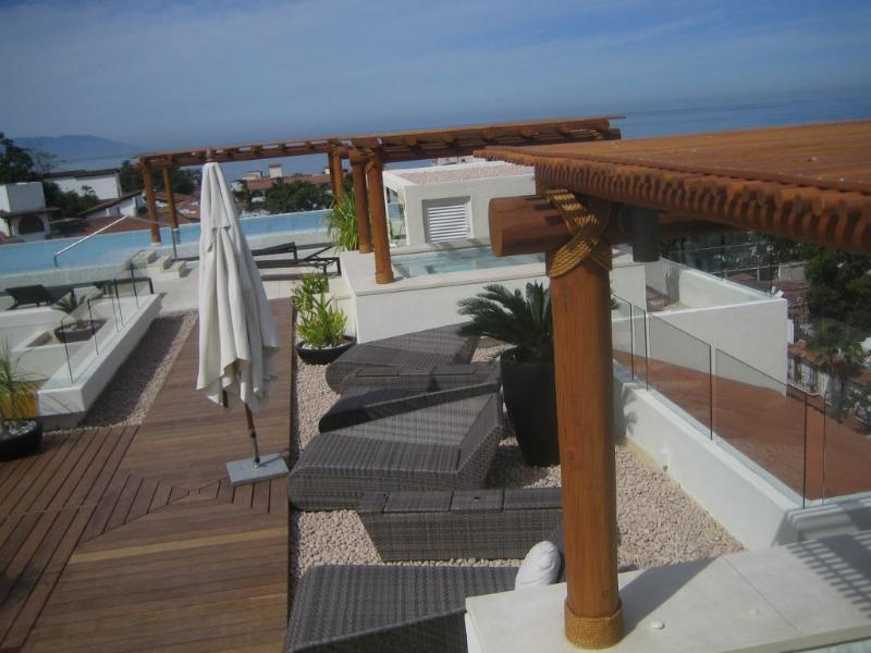 View of Jacuzzis and pool on rooftop shared terrace