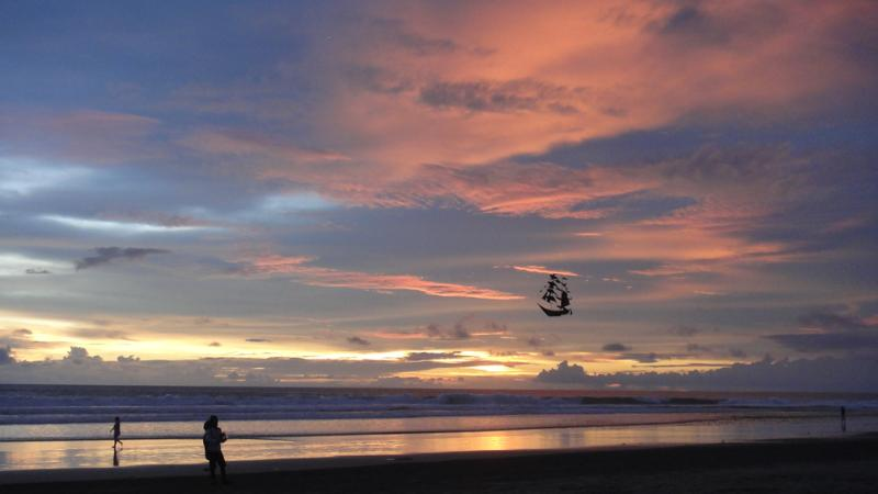 Kite flying on the beach at sunset.