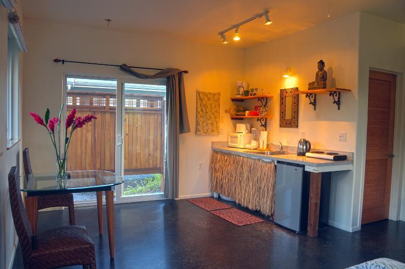 Mesa de comedor de vidrio - baño está detrás de la puerta tipo persiana.