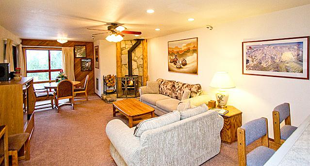 Aspen Creek #208 Living Area has an LED tv, Wood Burning Fireplace, and Dining Table Toward View