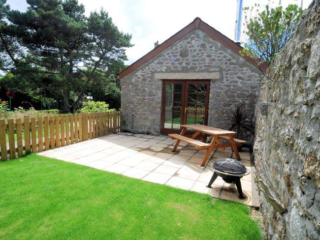 View towards the property across the enclosed garden/patio with seating