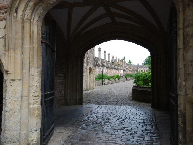 Ver a través del arco hacia el jardín de la catedral de Wells