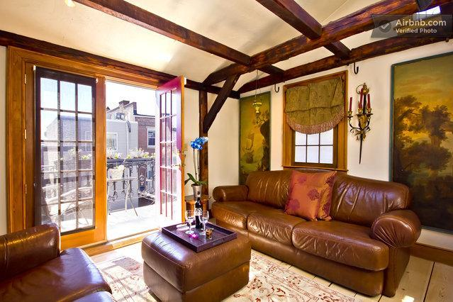 Elegant sitting room with fireplace, skylights, beams, cathedral ceiling, French style balcony