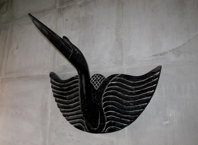 Antique black wooden bird for hanging towels in the bathrooms