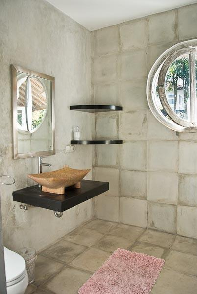 Second and thrid contemporary bathroom with round windows with a beautiful view of tropical palm trees