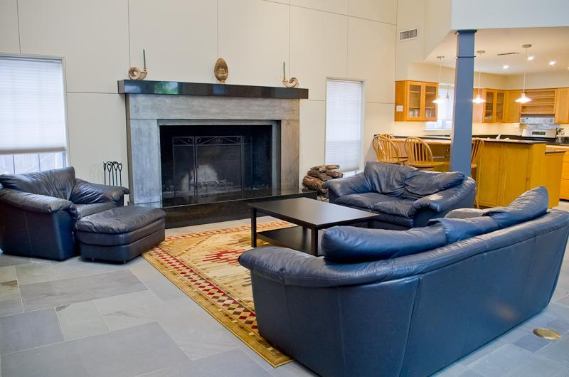 Spacious living room with two story ceilings and grand fireplace