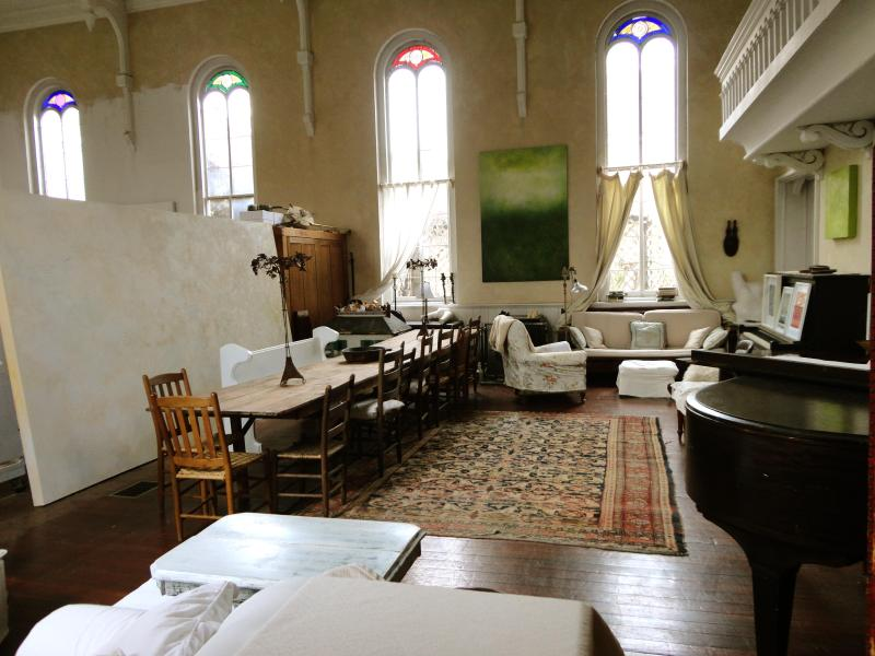 The church hall with a 17' harvest table and comfortable couches for gathering & two pianos