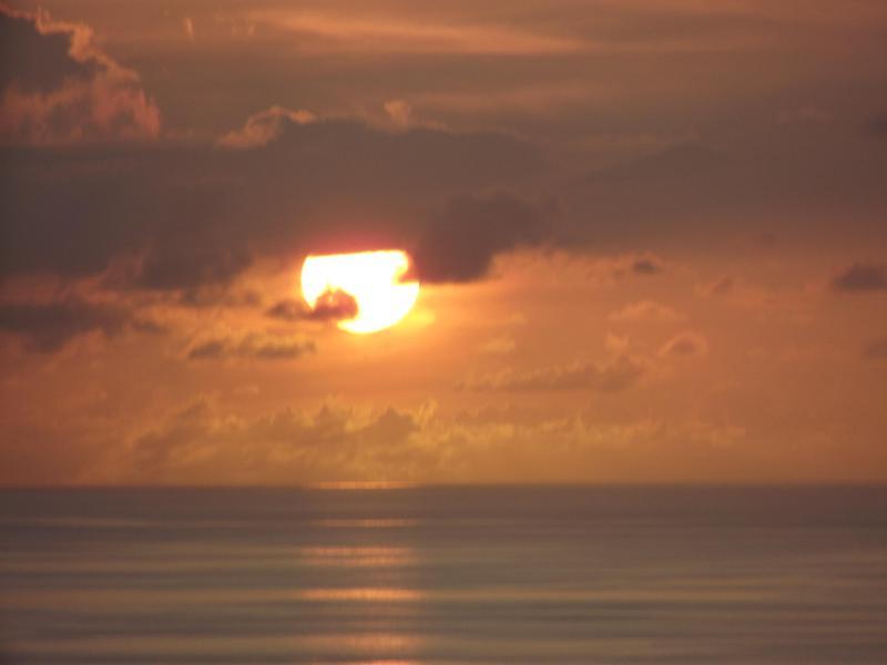 The sun setting over the Caribbean Sea by Pinney's Beach