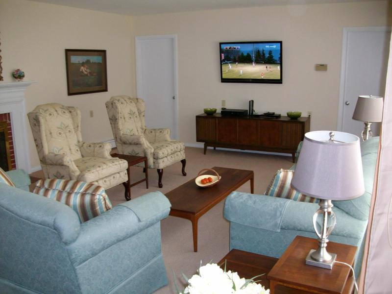 Living Room view with entrance to Kitchen and Dining Room. Large screen HDTV