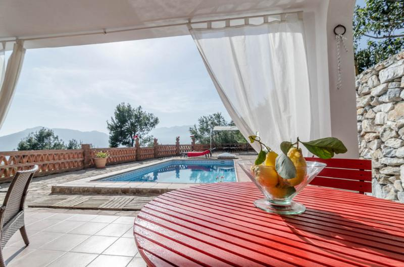 Outside dinning table with pool and sea view