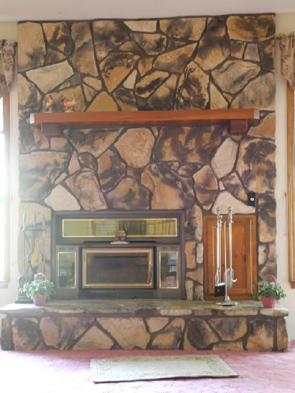 Living room fireplace with room warming insert